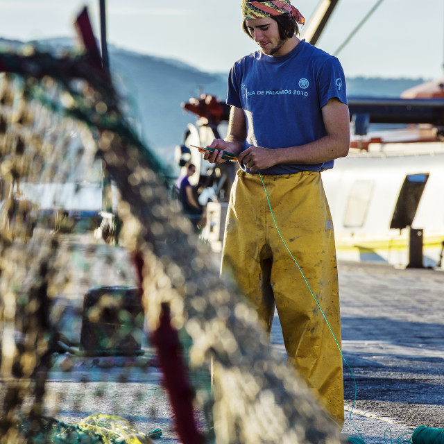 """Young fisherman mending fishing nets, Palamos, Spain"" stock image"