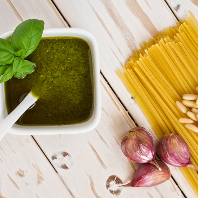 """""""Closeup of pesto genovese and linguine pasta, pine nuts and garlic on a table"""" stock image"""
