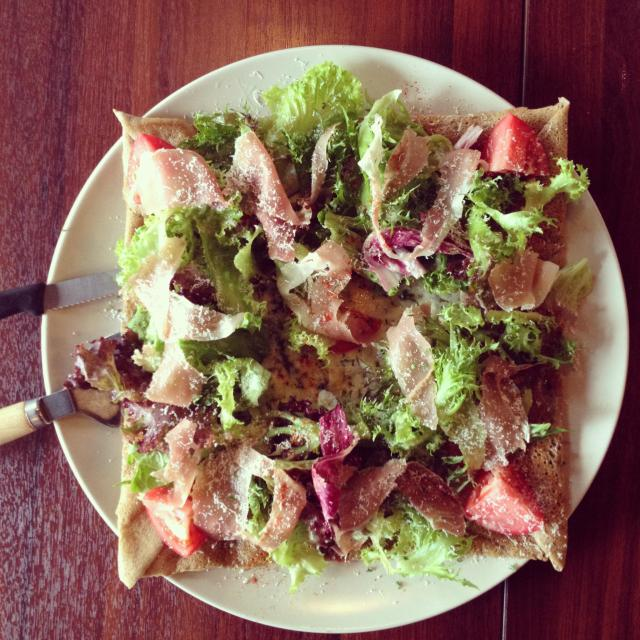 """""""French style savory galette topped with salad and prosciutto in natural light."""" stock image"""