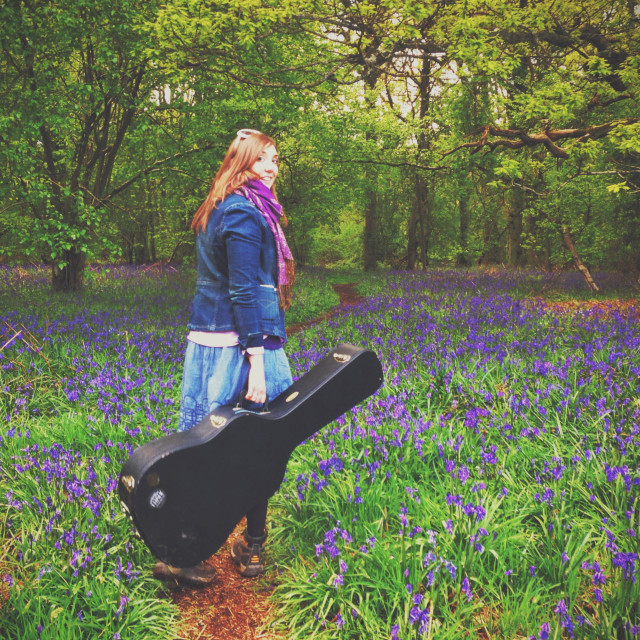 """Woman walking with guitar among bluebells"" stock image"