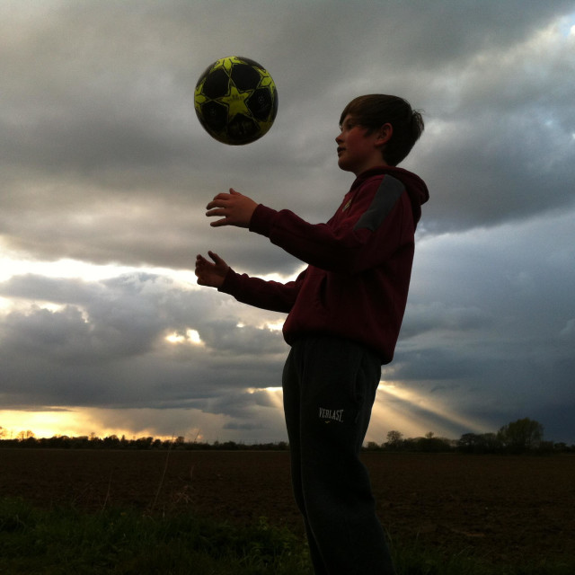 """""""A boy silhouetted against the sky uses his skills, concentration and balance to keep a football up in the air."""" stock image"""
