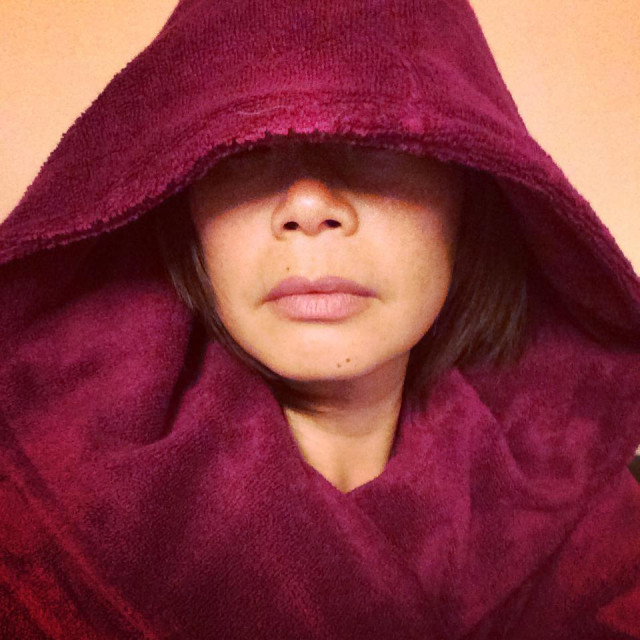 """""""Face of Woman in fuschia garment with hood draw over eyes"""" stock image"""