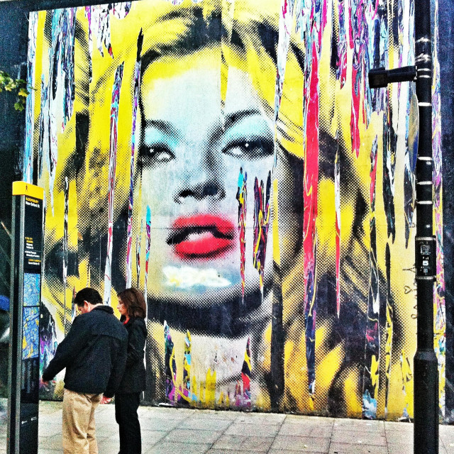 """""""A couple are dwarfed by a paste-up of model Kate Moss, by street artist Mr Brainwash (Thierry Guetta). The work was pasted to the outside of the Old Sorting Office as part of the artist's solo show."""" stock image"""