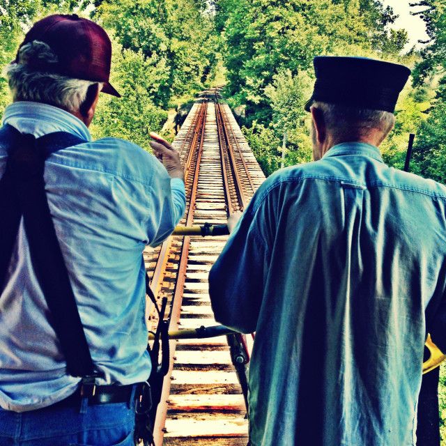 """""""A brakeman and conductor peer off the caboose end of a train."""" stock image"""