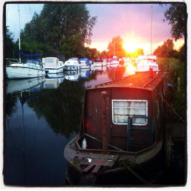 """""""Boats moored on The Chelmer and Blackwater Canal in Essex at sunset."""" stock image"""