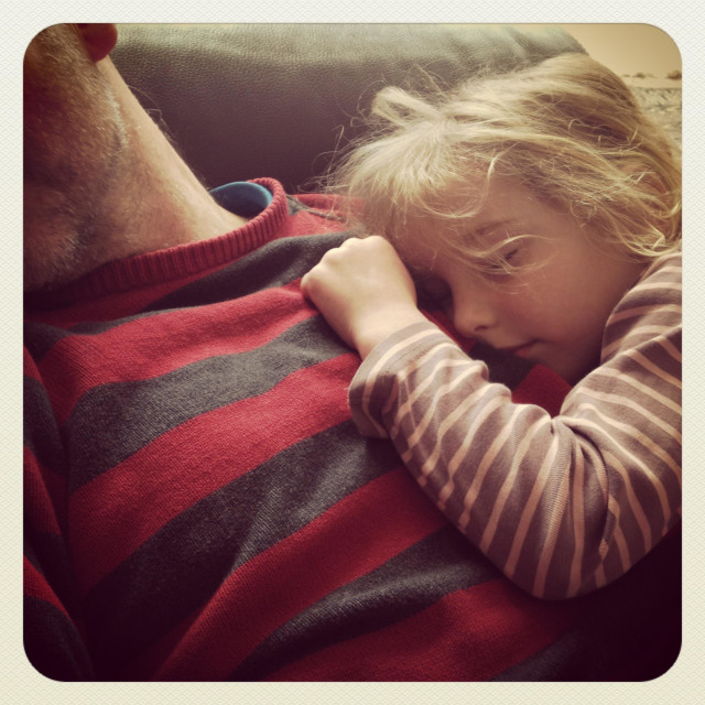 """""""A daughter asleep on her father's chest"""" stock image"""