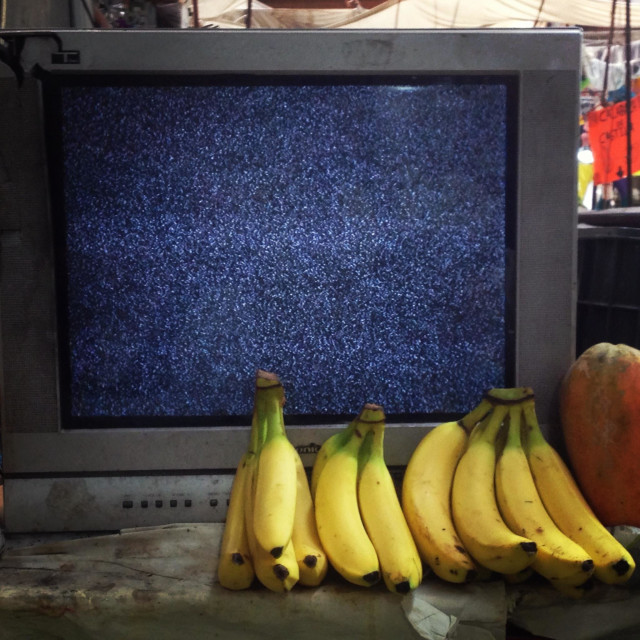 """A detuned television showing static noise sits in a vegetable shop in Mexico City, Mexico"" stock image"