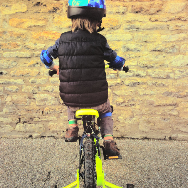 """""""Rear view of 4 year old boy riding small bicycle into a stone wall. Dead end. Going nowhere. Photo Credit - © COLIN HOSKINS."""" stock image"""