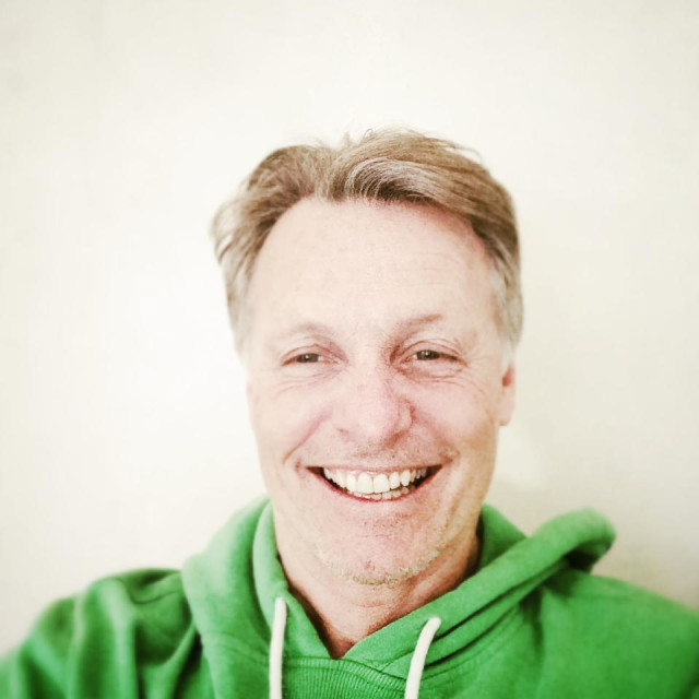 """Happy smiling mature man in his forties wearing a green hooded top."" stock image"