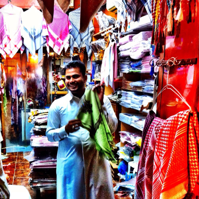 """Smiling cloth salesman in Arab souk invites customers to inspect his wares"" stock image"