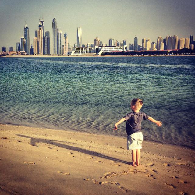"""Boy overlooking Dubai Marina from Palm Jumeirah beach"" stock image"