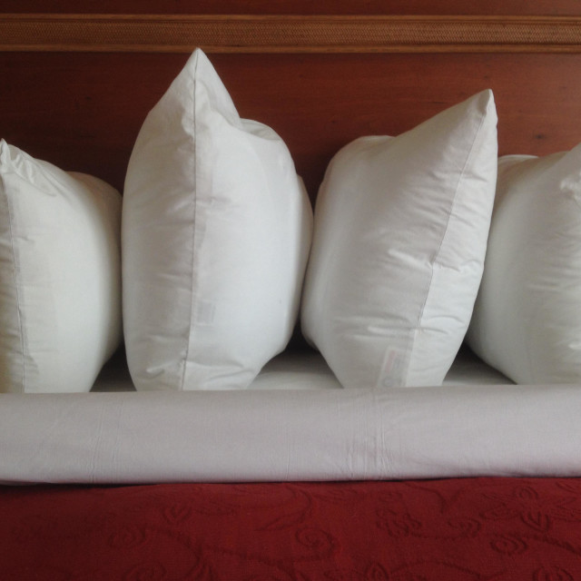 """""""Hospitality in bed: Four pillows by wooden baseboard in window light"""" stock image"""