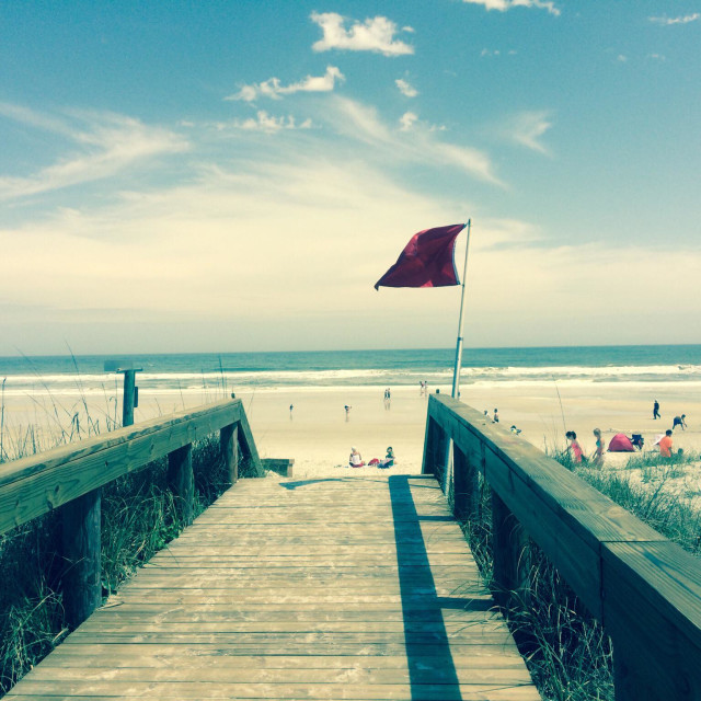 """Red warning flag flying at Jacksonville Beach, Florida"" stock image"