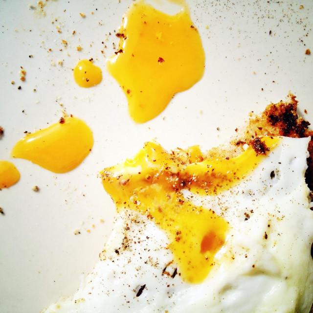 """Fried egg on toast, half eaten"" stock image"