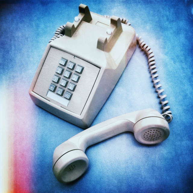 """Punch button land line retro office phone with handset off."" stock image"
