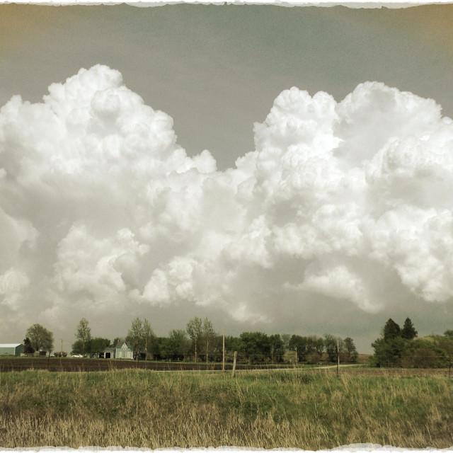 """A large storm cloud over a farm."" stock image"