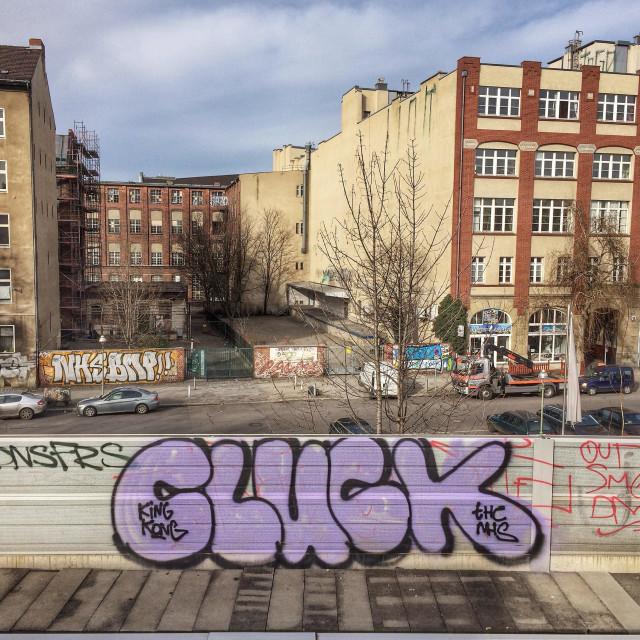 """Berlin graffity on railway bridge overlooking street with old buildings"" stock image"
