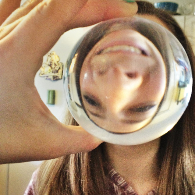 """""""Girl holding up crystal ball showing upside down funny face"""" stock image"""