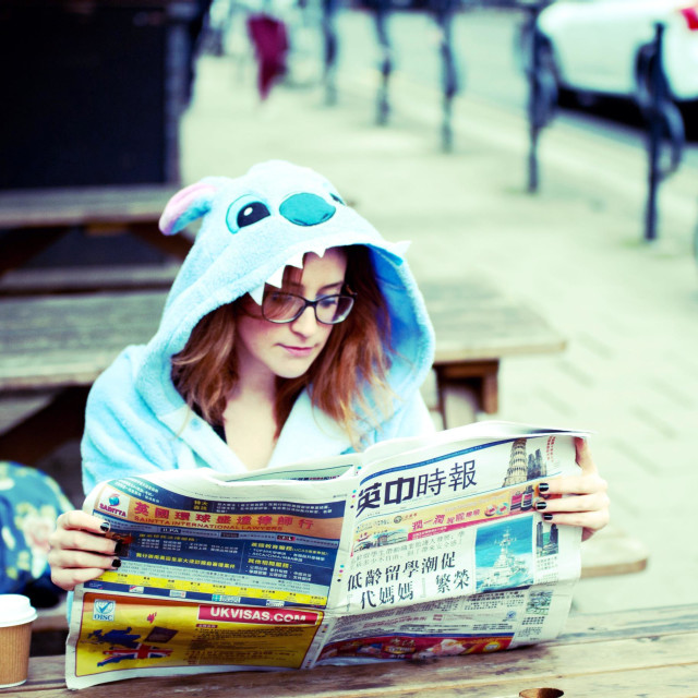 """Woman in Stitch costume reading a Chinese newspaper"" stock image"