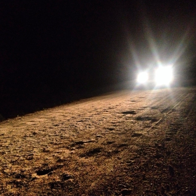 """""""A car drives at night in a dirt road in Prado del Rey, Cadiz province, Andalusia, Spain"""" stock image"""