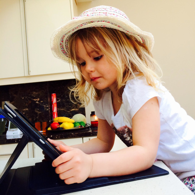 """""""Small girl with a hat on looking at an iPad"""" stock image"""