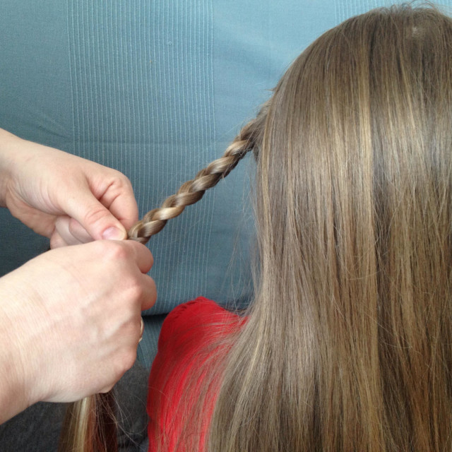 """""""Mother making a braid"""" stock image"""