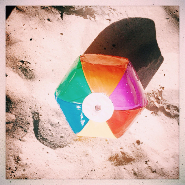 """A beach ball on the sand waiting for someone to play"" stock image"