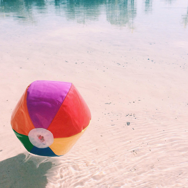 """A beach ball floating in water - summertime in Queensland"" stock image"