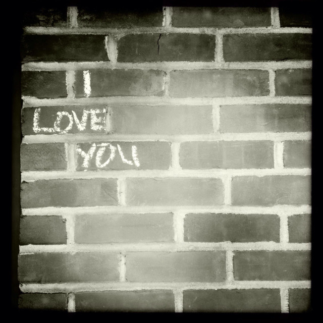 """""""The words I Love You written with white chalk on a brick wall."""" stock image"""
