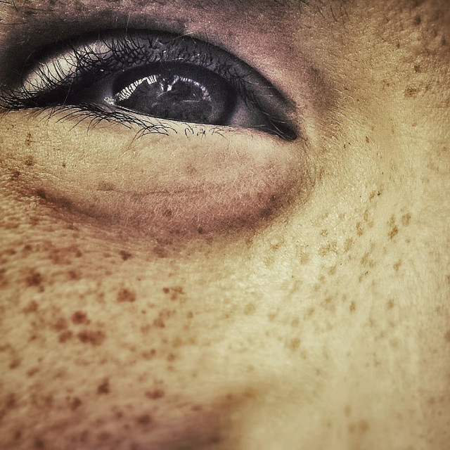 """""""Freckled eye smiling. Close up half face of young cheeky boy smiling."""" stock image"""