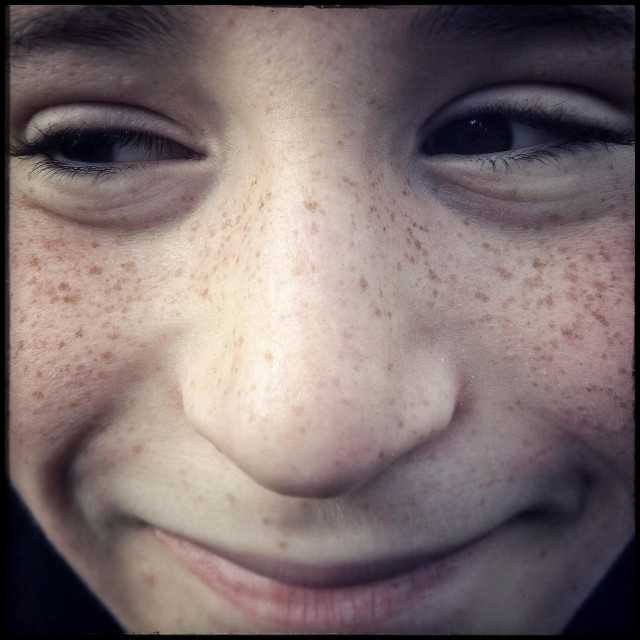 """""""Close up face of young cheeky boy smiling"""" stock image"""