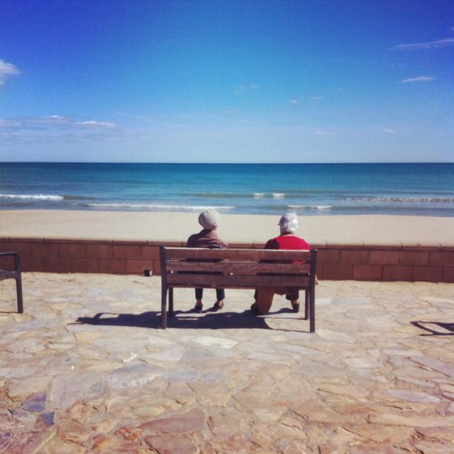 """Two elderly sitting in front of the sea in Vilanova i la Geltru, Barcelona Spain"" stock image"