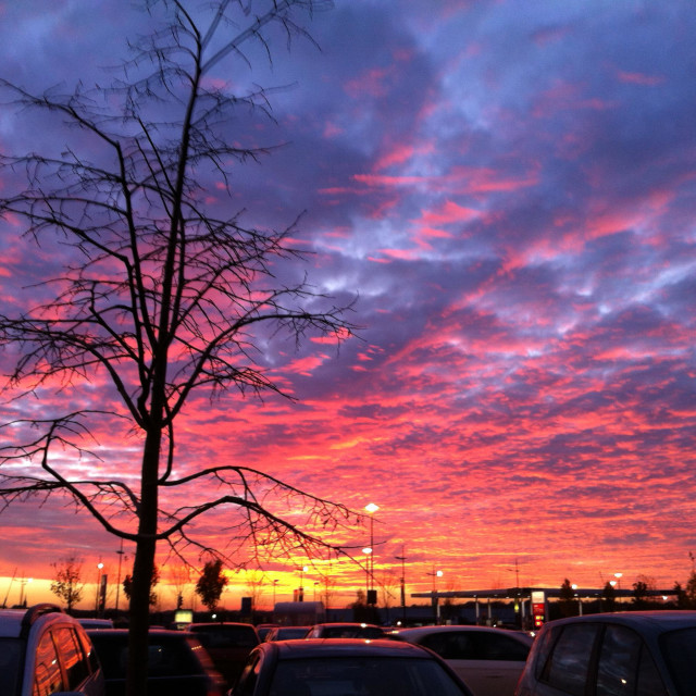"""Dramatic sunset seen over a car park"" stock image"