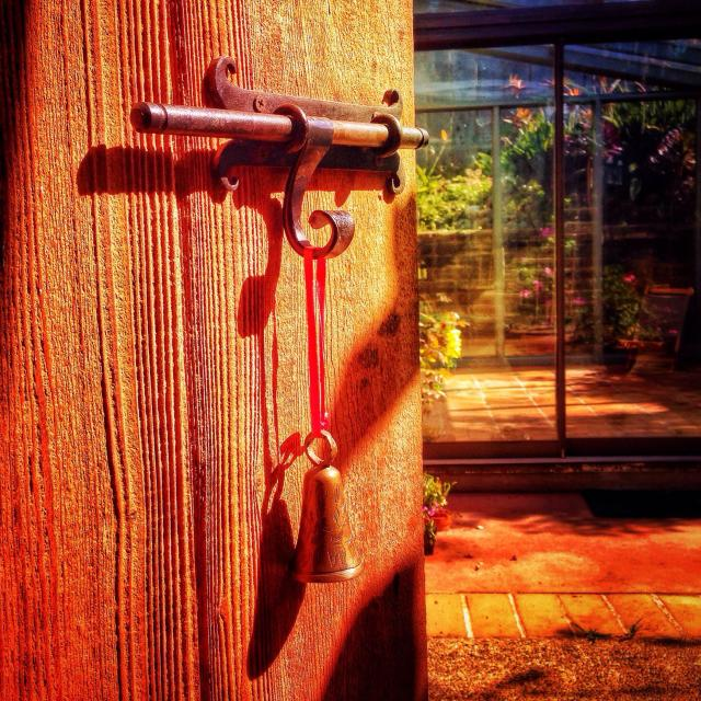 """Elaborate wrought iron latch on old hardwood door."" stock image"