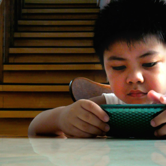"""""""Asian child boy watching or playing on a tablet phone"""" stock image"""