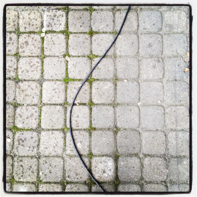"""The water hose on a square tile pavement"" stock image"