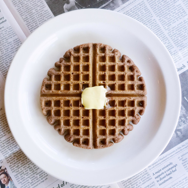 """""""A gluten free waffle for breakfast, on a plate with a knob of butter and the morning newspapers."""" stock image"""