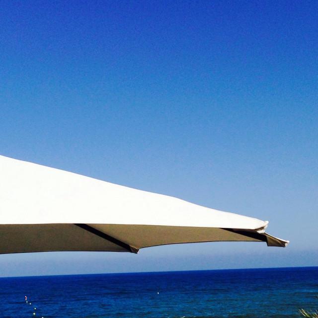 """Sun umbrella white facing the blue sea under a blue sky creating an abstract image."" stock image"
