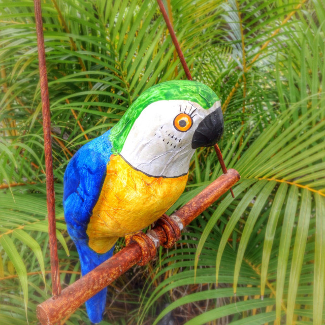 """Paper mâché parrot on perch in palm branches"" stock image"