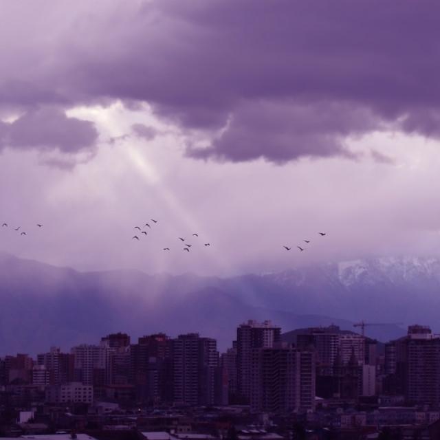 """""""Nubes con rayo de luz, pajaros y ciudad"""" stock image"""