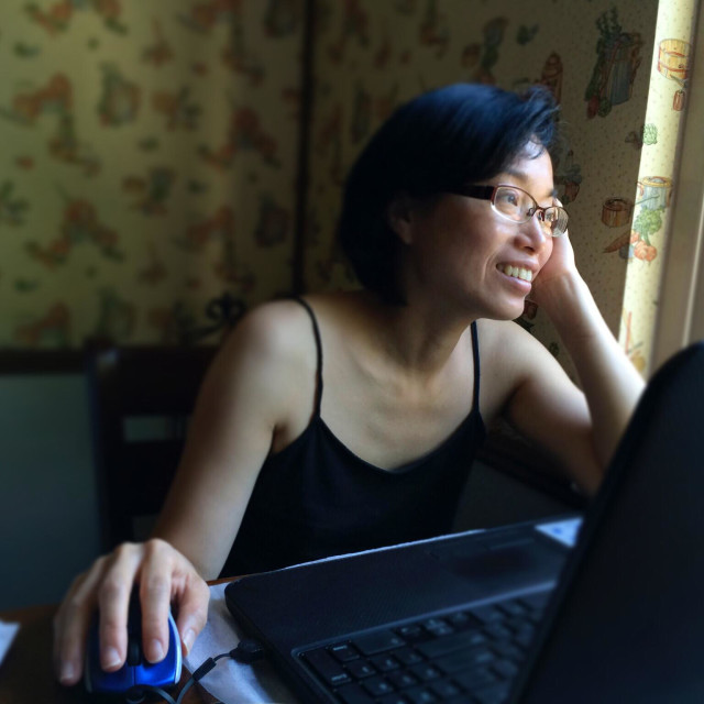 """""""Asian woman smiling and looking out a window while using a laptop computer at home"""" stock image"""