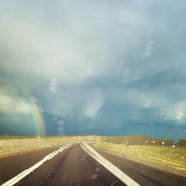"""Rainstorm with rainbow on Wyoming road"" stock image"