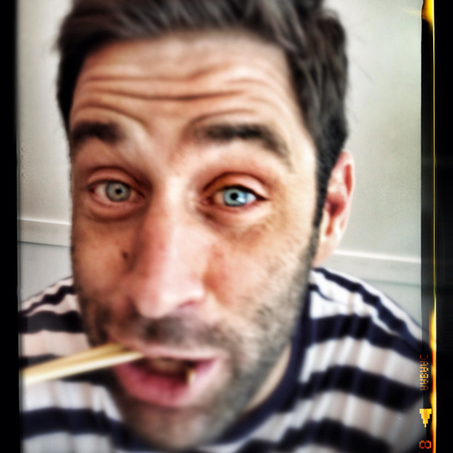 """""""Guy using chopsticks in black and white striped shirt"""" stock image"""