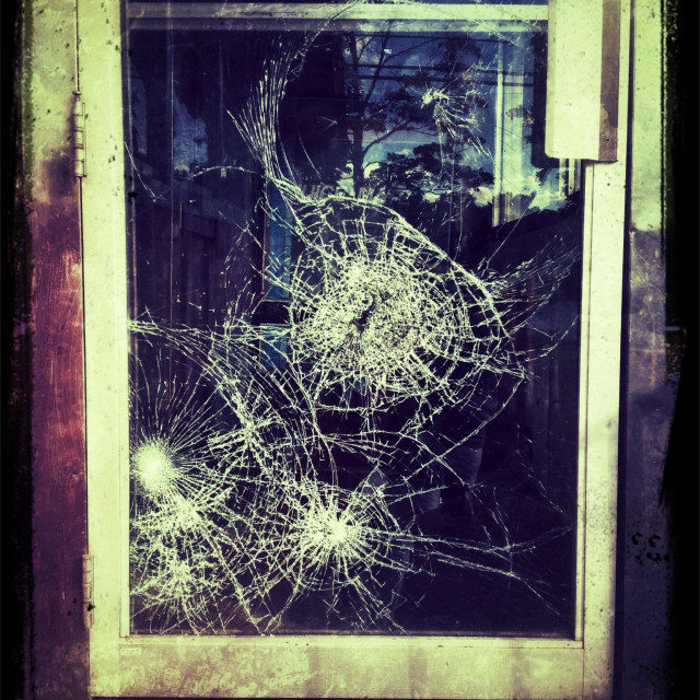 """Broken glass on front door of abandoned storefront"" stock image"
