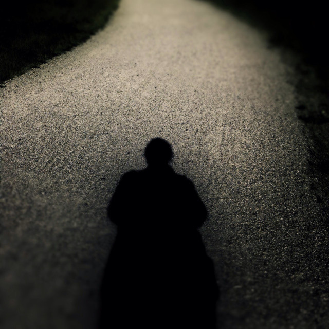 """Silhouetted figure on winding path."" stock image"
