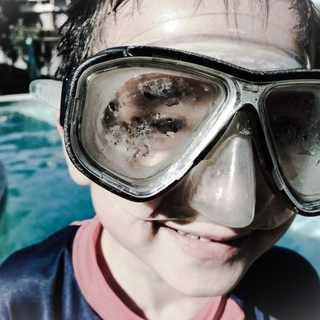 """""""6 year old boy wearing a dive mask by a swimming pool."""" stock image"""