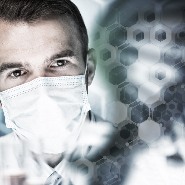 """""""Young scientist mixing reagents in glass flask in clinical laboratory"""" stock image"""