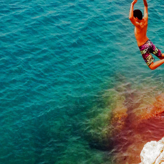 """""""Boy leaping off a cliff into the sea"""" stock image"""