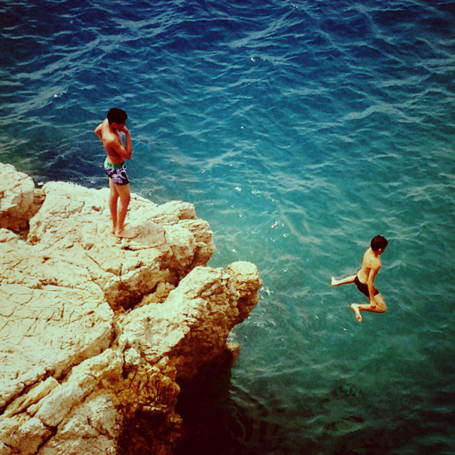 """""""Two boys diving off a cliff"""" stock image"""