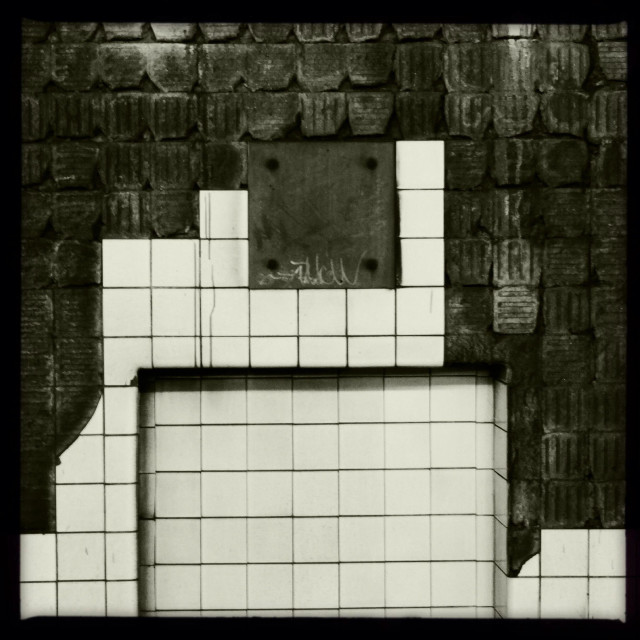 """Subway. Wall of the tunnel at the 21st station of the G line in Queens, NY. Tiles are falling off leaving interesting designs in the wall"" stock image"